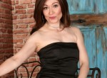 Mature Kitty removes her black dress and poses.